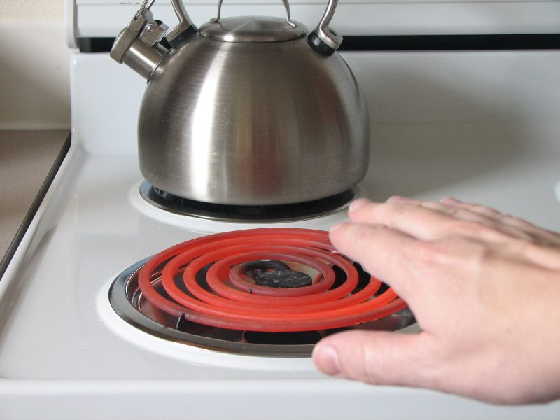Hand approaches red-hot burner on electric range with kettle in background.